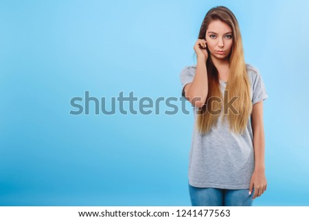 Girl in gray clothes on a blue background touches the ear. Concept attentive, body language, sign, distraction attention. Copy space left. #1241477563