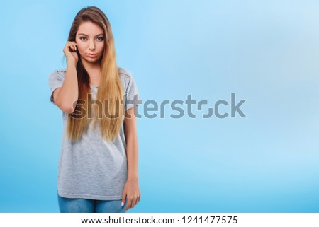 Girl in gray clothes on a blue background touches the ear. Concept attentive, body language, sign, distraction attention. Copy space right. #1241477575