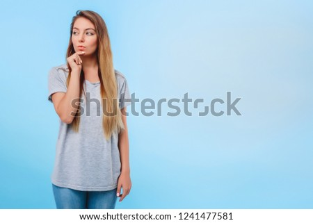 Girl blue background gray t-shirt conceived to fulfill plans for evening. Meeting with girlfriends and shopping in store. Concept of end of study and weekend. #1241477581