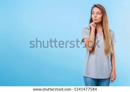 Girl blue background gray t-shirt conceived to fulfill plans for evening. Meeting with girlfriends and shopping in store. Concept of end of study and weekend. Copy space left. #1241477584