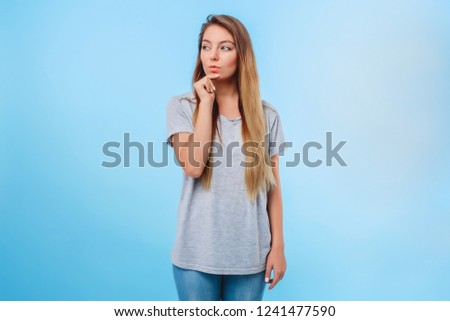 Girl blue background gray t-shirt conceived to fulfill plans for evening. Meeting with girlfriends and shopping in store. Concept of end of study and weekend. #1241477590