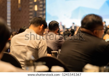 Closeup Interpreter Headset of Rear view of Audience who is wearing and listening Speakers via  on the stage in the conference hall or seminar meeting, business and education about investment concept Royalty-Free Stock Photo #1241541367