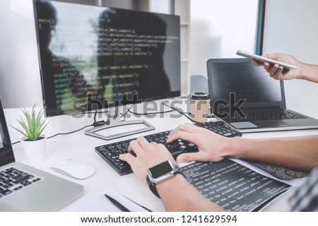 Programmers cooperating at Developing programming and website working in a software develop company office, writing codes and typing data code. #1241629594