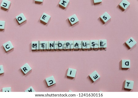 Menopause word made of square letter word on pink background. #1241630116