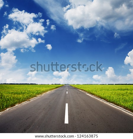 asphalt road through the green field and clouds on blue sky in summer day #124163875