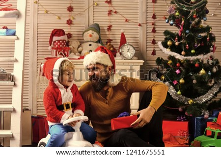 Happy family celebrate new year and Christmas. Father and child on car with new year present box. Winter holiday and boxing day. Father and son in santa hat at Christmas tree. Xmas party celebration. #1241675551