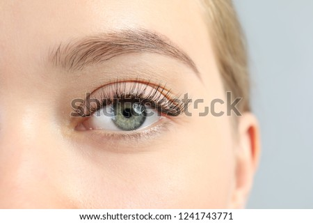 Young woman with beautiful long eyelashes on gray background, closeup. Extension procedure #1241743771