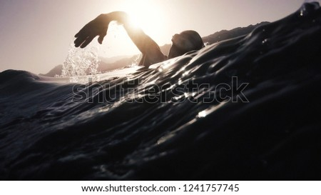 professional young swimmer athlete doing morning swimming freestyle practice at sunrise in open sea. vintage film stylized  #1241757745