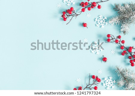 Christmas or winter composition. Frame made of snowflakes, fir tree branches and red berries on pastel blue background. Christmas, winter, new year concept. Flat lay, top view, copy space #1241797324