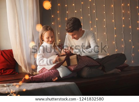 Boy and girl friends or brother and sister open a gift and smiling sitting near the window in the Christmas interiors. The concept of Christmas and New Year. Winter time. #1241832580