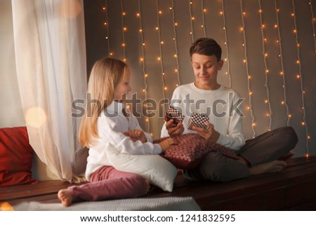 Boy and girl friends or brother and sister open a gift and smiling sitting near the window in the Christmas interiors. The concept of Christmas and New Year. Winter time. #1241832595