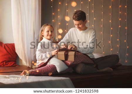 Boy and girl friends or brother and sister open a gift and smiling sitting near the window in the Christmas interiors. The concept of Christmas and New Year. Winter time. #1241832598