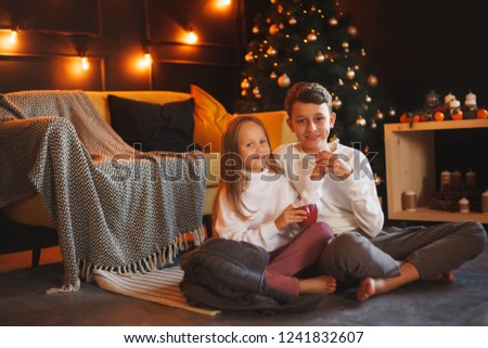 Boy and girl friends or brother and sister сuddling and smiling in the Christmas interiors. The concept of Christmas and New Year. Winter time. #1241832607