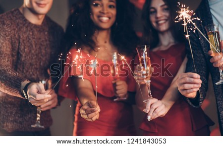 Multiracial friends celebrate new year and holding bengal lights and glasses with drink. #1241843053
