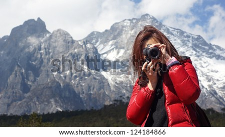 Young girl photographer holding camera DSLR, she force on other, with snow mountain Jade Dragon background in Lijiang,  in winter, in Yunnan China wide mountain range