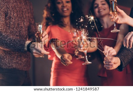 Crossing sticks. Multiracial friends celebrate new year and holding bengal lights and glasses with drink. #1241849587