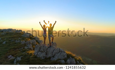 DRONE, LENS FLARE: Flying over sporty couple outstretching arms after a successful hike in the scenic mountains in Slovenia. Cheerful young tourists outstretching arms on a golden summer evening. #1241855632