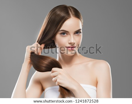 Smooth long brunette hair woman healthy and strong with healthy clean skin  female over gray background #1241872528