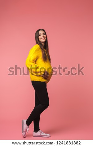 Image of a beautiful young pregnant emotional woman posing isolated over pink background.