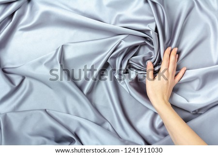 Female hand touching smooth elegant silk or satin luxury cloth texture #1241911030