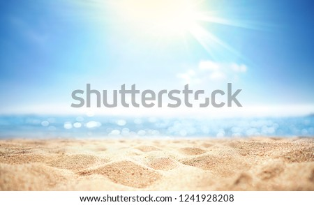 Abstract blur defocused background, nature of tropical summer beach with rays of sun light. Golden sand beach, sea water against blue sky with white clouds. Copy space, summer vacation concept.