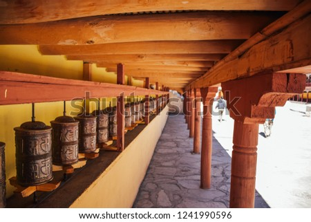 High angle view of rows on prayer wheel in Hemis Monastery, Leh Ladakh, India. The spinning of the prayer wheel is said to bring peace and calm. The prayer wheels are in monasteries with sacred mantra #1241990596