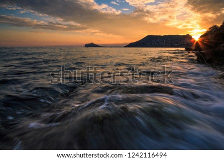 rocky seashore during sunset and at night #1242116494