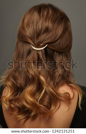 Close up isolated portrait of a lady with wavy ombre hair. The back view of the girl with half-up hairstyle, adorned with pearl-studded golden half moon barrette. Posing over the grey background. #1242131251