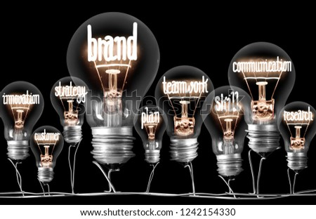 Photo of light bulbs with shining fibres in shape of BRAND concept related words isolated on black background #1242154330