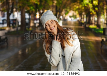 Cheerful young woman dressed in autumn coat and hat walking outdoors at the city street #1242156493