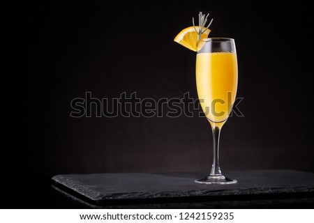Mimosa cocktail in a champagne glass with orange juice and sparkling wine decorated with lavender leaves and orange slices #1242159235