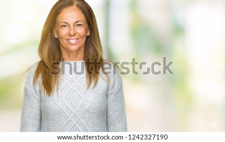 Beautiful middle age adult woman wearing winter sweater over isolated background with a happy and cool smile on face. Lucky person. #1242327190
