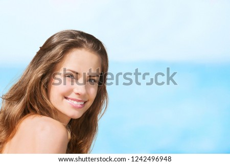 Young smiling woman on blurred ocean background #1242496948