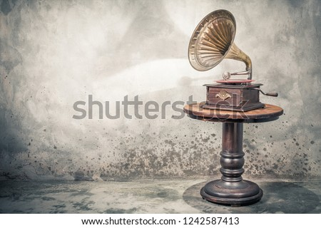 Vintage antique gramophone phonograph turntable with brass horn and red color vinyl disc record on wooden table front concrete wall background with shadow. Retro old style filtered photo Royalty-Free Stock Photo #1242587413