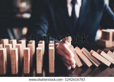 Business risk control concept, Businessman protect wooden block fall to planning and strategy in risk to business Alternative and prevent. Investment Insurance Business. #1242616783