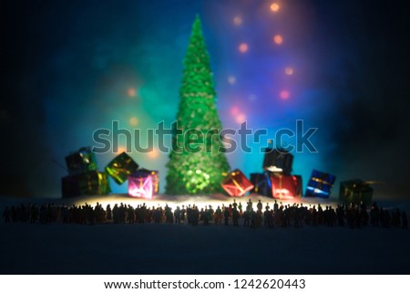 New year or Christmas holiday shopping concept. Store promotions. Silhouette of a large crowd of people watching at a big fir tree and gift boxes. People on snow ready to shopping. Selective focus