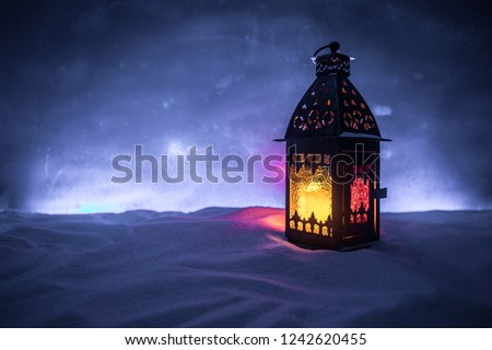 Christmas lantern on snow at night. Festive dark background. New Year's still-life postcard lamp covered in snow with glowing candle at night. Holiday concept. Artwork #1242620455