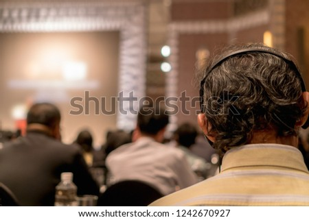 Closeup Interpreter Headset of Rear view of Audience who is wearing and listening Speakers via  on the stage in the conference hall or seminar meeting, business and education about investment concept Royalty-Free Stock Photo #1242670927