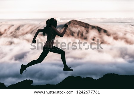 Trail runner athlete silhouette running in mountain summit background clouds and peaks background. Woman training outdoors active fit lifestyle. #1242677761