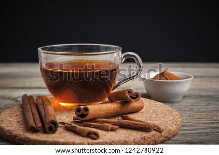 aromatic hot cinnamon tea on wooden table Royalty-Free Stock Photo #1242780922