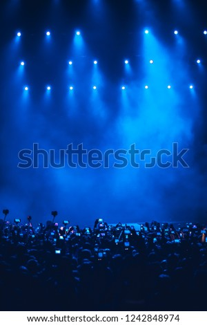 Concert crowd of fans taking pictures on event in music hall.Bright blue stage lights on rock festival in nightclub.Group of people shoot videos with smart phone cameras on musical party in big club