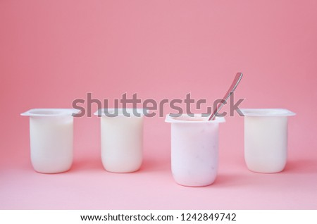 Four yogurts in white plastic cups on pink background with copy space. Strawberry pink yoghurt with spoon in it. Minimal style. Concept of better choice. #1242849742