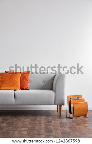 Vertical view of grey comfortable couch with orange pillows and newspaper rack next to it, real photo with copy space on the white wall #1242867598
