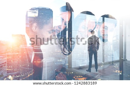 Rear view of young businessman looking at cityscape from his office window. Double exposure of business team. Concept of leadership. Toned image #1242883189