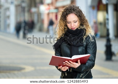 young woman reads a book on a street in winter #1242885493
