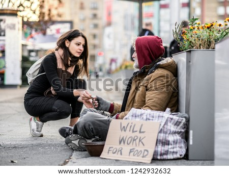 Young woman giving money to homeless beggar man sitting in city. #1242932632