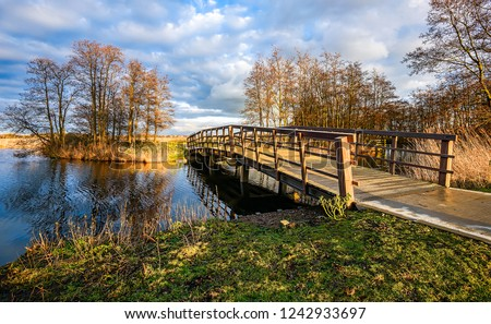 Autumn rural river bridge landscape. Rural river bridge in autumn. Rural river bridge view. Rural bridge river scene #1242933697