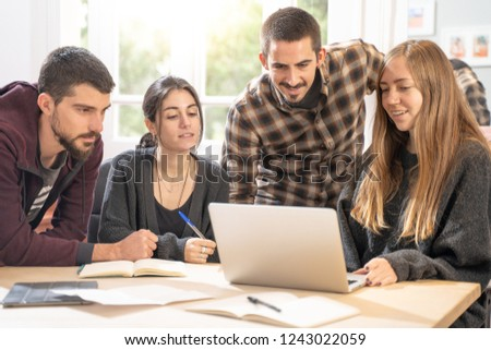 Happy young university students studying with laptop in library. Group of multiracial people in college library sitting together at table with books and laptop. Happy young people.  #1243022059