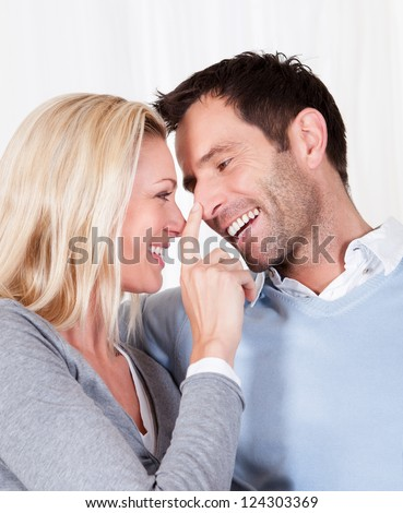 Laughing attractive woman touching her husband affectionately on the nose with the tip of her finger #124303369
