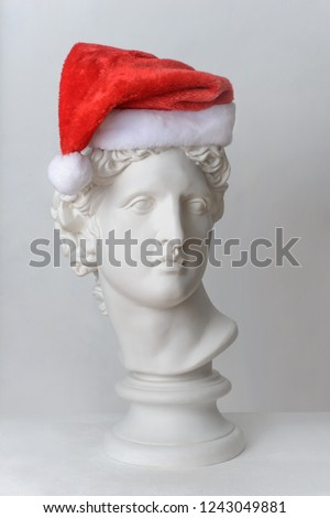 Statue. Isolated. Head. Gypsum statue of Apollo's head.  Statue Apollo's head in Santa Claus hat isolated on white background. Christmas and New Year celebration. Christmas hats. Apollo Belvedere #1243049881